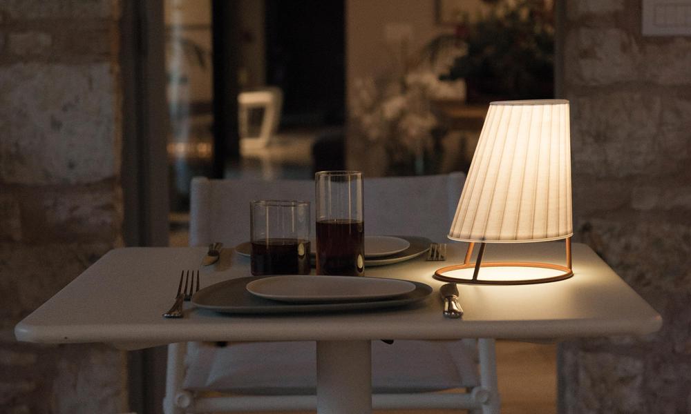 Una lampada Cone di Emu piccola illumina un tavolo apparecchiato