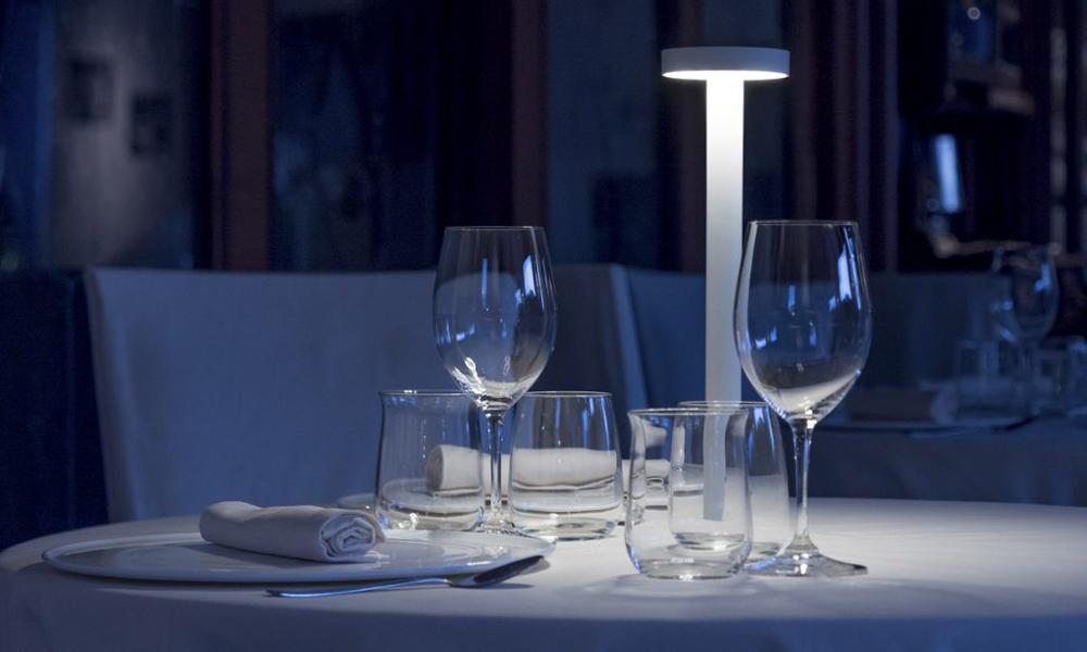Una lampada Tet a Tet di Davide Groppi illumina un tavolo apparecchiato